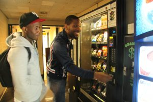 Two students make a selection at a vending machine in Shuster Hall.